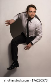 Handsome Young Bearded Businessman Climbing Out Of A Circular Hole In A White Wall In A