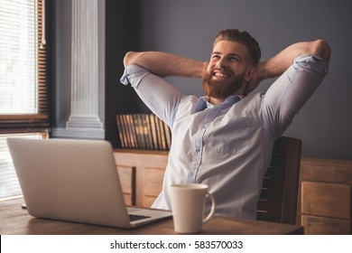 Handsome young bearded businessman is smiling while relaxing on chair in office
