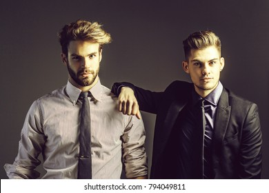 Handsome young bearded businessmen friends in jacket, shirt and tie has fashionable hair and serious face on grey background. Stylish sexy men or guys in studio