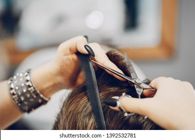 handsome young bearded guy sitting in an armchair in a beauty salon and the girl near him cuts his hair