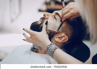 handsome young bearded guy sitting in an armchair in a beauty salon and the girl near him shrugs his neck
