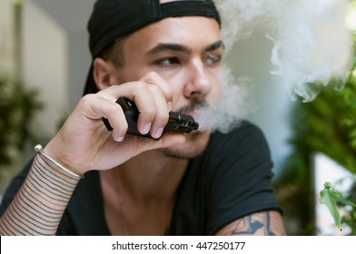 handsome young bearded man holds an electronic cigarette (e-cig) and exhaling a cloud of vapor. guy vaping in sunglasses with tattoos