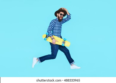 Handsome young bearded man jumping with yellow skateboard against the colorful wall. Hipster with beard in motion on blue background