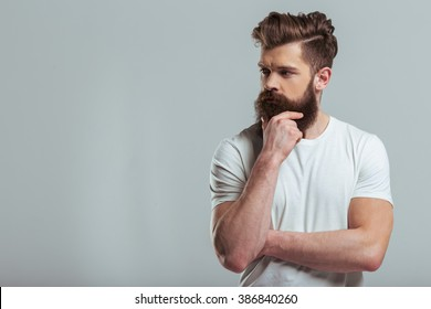 Handsome young bearded man is keeping hand on beard and looking away, on a gray background