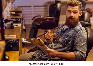 Handsome young bearded man reading a magazine and holding a glass of beverage while sitting on a chair at the barber shop