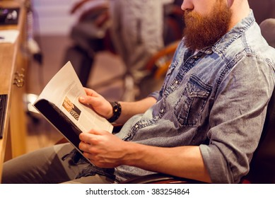 Handsome young bearded man reading a magazine while sitting on a chair at the barber shop, close-up