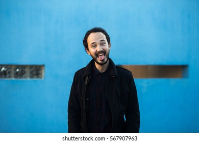Handsome young bearded man, showing tongue, on the blue wall background. With shallow depth of field.