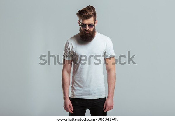 Handsome young bearded man in sunglasses is looking at camera while standing against gray background