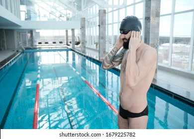Handsome young bearded man with tattoo adjusting ears in swimming cap while preparing for swimming
