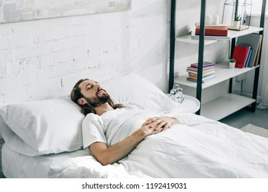 handsome young bearded man waking up in bedroom at home