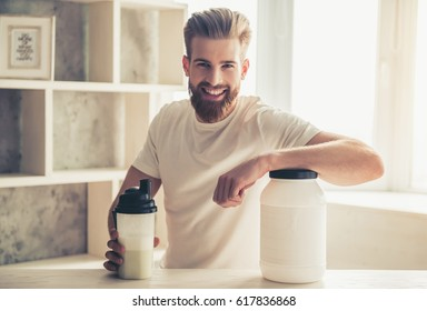 Handsome young bearded sportsman is looking at camera and smiling while preparing sport nutrition in kitchen at home