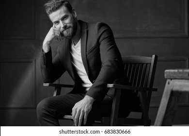 Handsome young beautiful and confident bearded man, wearing white shirt and brown jacket, sitting on wooden chair in studio with dark background and smiling, in black and white