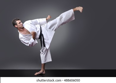 Handsome young black belt male karate doing kick on the gray background