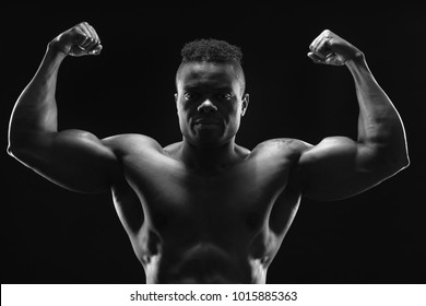 A handsome young black bodybuilder flexing his biceps. Double biceps pose. Front view. Monochrome image.