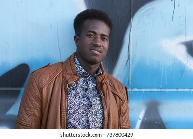 Handsome young black man in front of blue and black painted metal surface