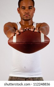 handsome young black man holding a football out to the camera with thoughtful, and serious eye contact