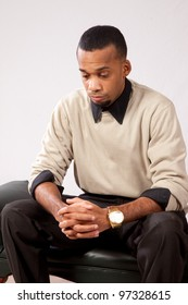 Handsome young black man sitting with a feeling of sadness and looking down