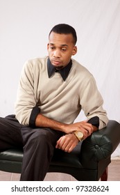 Handsome young black man sitting with a feeling of sadness and leaning against the edge of the bench he is sitting on