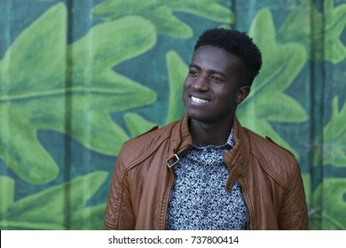 Handsome young black man smiles in front of wall painted with leaves