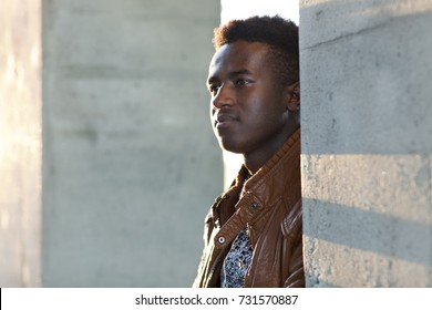 Handsome young black man stands in sunlight between concrete pillars