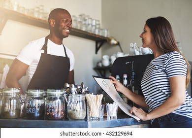 Handsome young Black restaurant owner in apron talking with cheerful female customer in striped shirt holding menu at counter