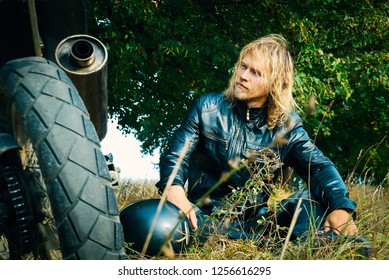 Handsome young blond guy sitting on the grass near his motorcycl