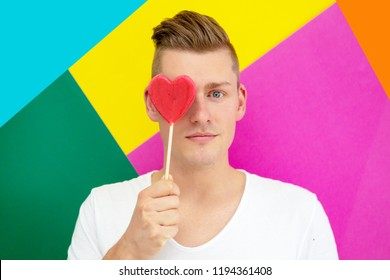 handsome young blond man holding a heart shaped lollipop