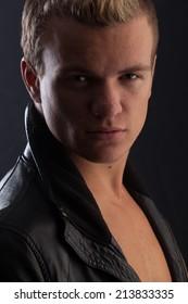 Handsome young blond man. Studio portraits against black background