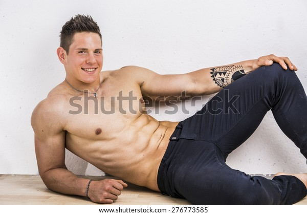 Handsome Young Bodybuilder Laying Down On The Stock Photo