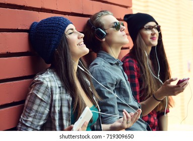 Handsome young boy and beautiful girls listening to the music with earphones and enjoying wih a smart phone outdoor near red bricks wall background.