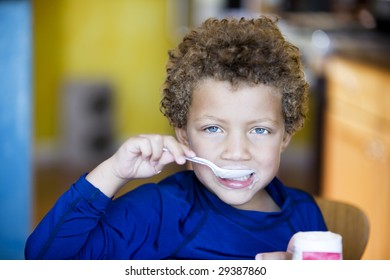Handsome young boy with blue eyes eating yogurt