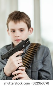 Handsome Young Boy with Bullet Belt Holding a Hand Gun with Serious Facial Expression.