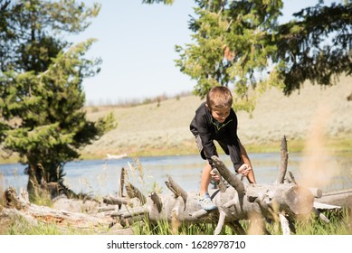 Handsome young boy climbing a log with river in background