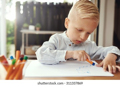 Handsome young boy drawing with crayons on sheets of white paper on a table on an open-air patio at home with a serious expression