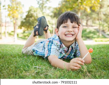 Handsome Young Boy Enjoying His Lollipop Outdoors on the Grass.