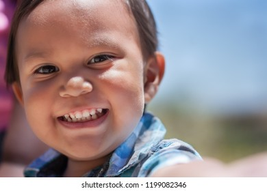 Handsome young boy with great smile and full set of baby teeth looking excited outdoors during summer