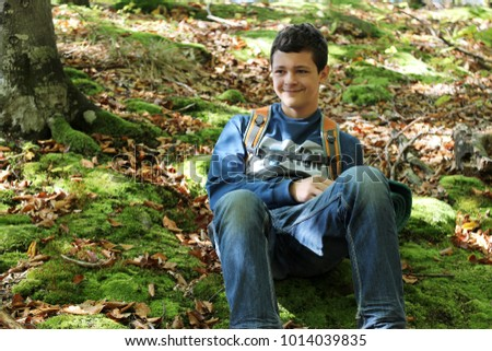 Handsome young boy in jeans and sportswear with backpack sitting on the  green moss during his 16a7588700894