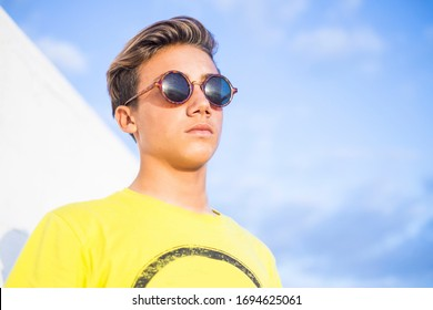 Handsome young boy man with blonde hair and black sunglasses stand and pose with yellow shirt and blue sky background - caucasian guy summer portrait