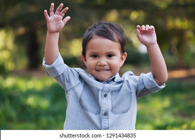 A handsome young boy, nicely dressed showing an expression of joy with hands up in the air looking excited and happy to be playing outdoors.
