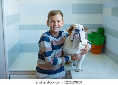 Handsome Young Boy wearing cozy pajamas Playing with His english funny bull Dog and enjoy life time weekend hanging each other with love and tender. Cactus toy.