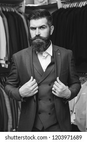 Handsome young brunette bearded model, wearing in black and white suit, looking with attitude, posing at shop. Businessman in classic black suit against row of suits in shop. Elegant clothes.