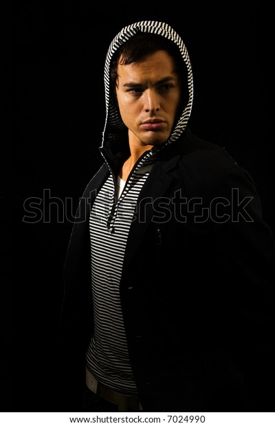 Handsome young brunette man wearing a hooded shirt and dark jacket on black
