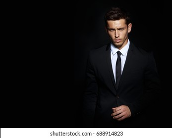 Handsome young brunette model, wearing in black and white suit, looking with attitude, posing at studio, isolated on black background. Business man portrait. Copy space. Horizontal view.