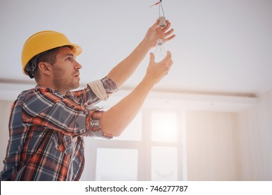 Handsome young builder in a yellow construction helmet is twisting the light bulb in. The man is looking up .