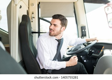Handsome young bus driver looking behind before starting tour trip