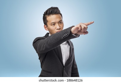 Handsome young business asian man pointing up