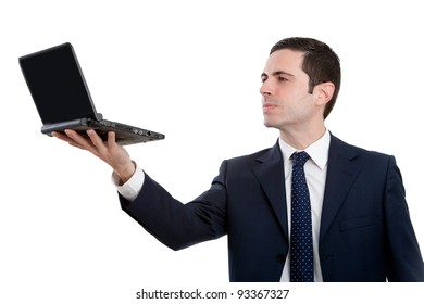 Handsome young business man in blue suit holding  laptop up high. Isolated on white.