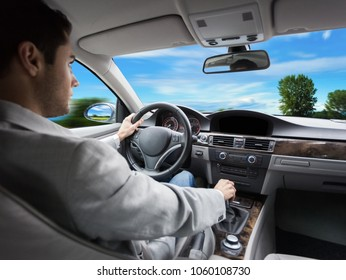 Handsome young business man driving his car