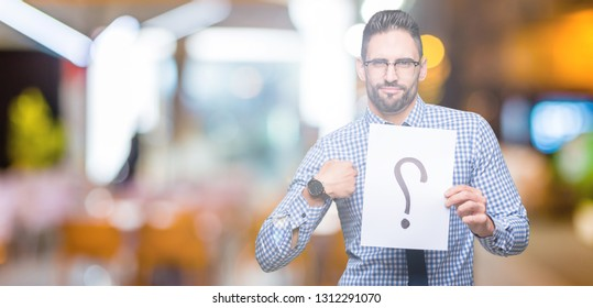 Handsome young business man holding paper with question mark over isolated background with surprise face pointing finger to himself