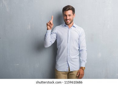 Handsome young business man over grey grunge wall wearing elegant shirt showing and pointing up with finger number one while smiling confident and happy.